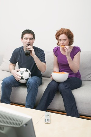 t off: Young couple with football, bottle of beer & crisps watching TV LANG_EVOIMAGES