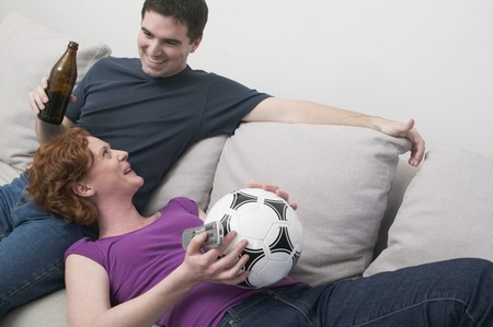 Young couple on sofa with football and bottle of beer