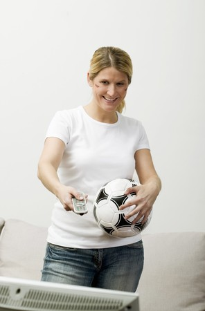 25 to 30 year olds: Young woman with football & remote standing in front of TV LANG_EVOIMAGES