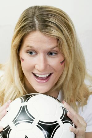 25 to 30 year olds: Young woman with German colours on her face holding football
