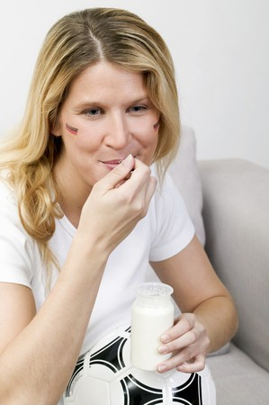 25 to 30 year olds: Young woman with football eating natural yoghurt LANG_EVOIMAGES