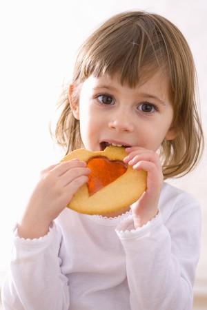 poco: Pequeña muchacha que come ventana galleta (galleta con ventana azúcar)