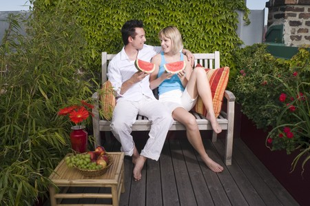 Couple sitting on a bench out of doors & eating watermelon LANG_EVOIMAGES