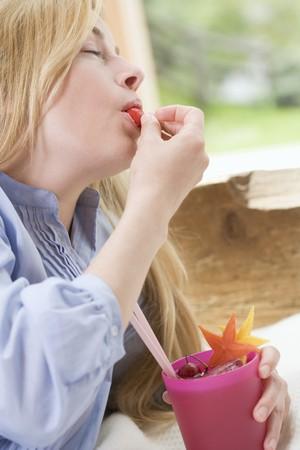 cocktail de fruits: Femme blonde mangeant le fruit d'un cocktail de fruits