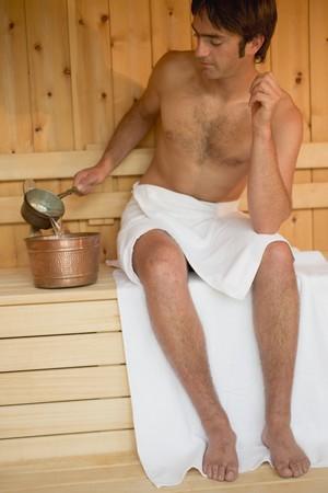 25 to 30 year olds: Man sitting beside sauna bucket in a sauna