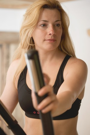 35 to 40 year olds: Blond woman working out on crosstrainer LANG_EVOIMAGES