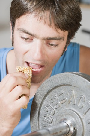 body consciousness: Man eating muesli bar on weight bench LANG_EVOIMAGES
