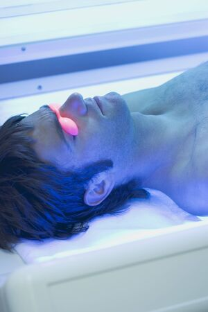 25 to 30 year olds: Young man in tanning goggles lying on tanning bed
