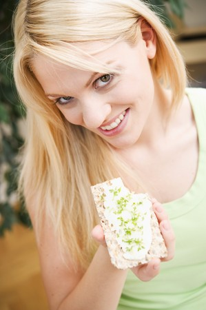 20 to 25 year olds: Young woman eating crispbread with quark and cress
