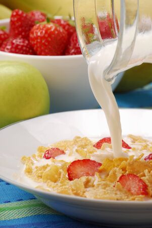 pouring milk: Pouring milk over cornflakes and strawberries