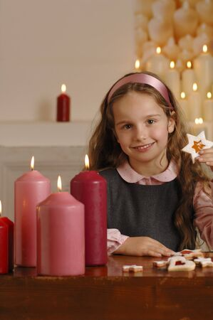 10 to 12 year olds: Girl with Christmas biscuits and candles