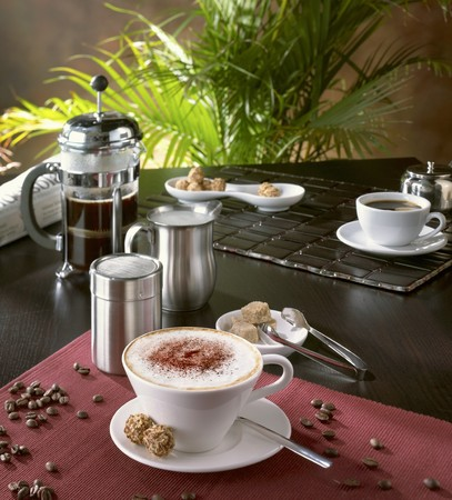 coffeepots: Cappuccino in caf� setting with coffee beans LANG_EVOIMAGES