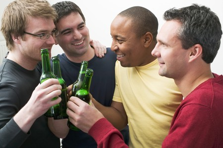 25 to 30 year olds: Four men clinking bottles of beer LANG_EVOIMAGES