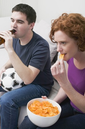 Young couple with football, bottle of beer & crisps watching TV LANG_EVOIMAGES
