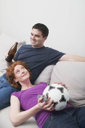 25 to 30 year olds: Young couple on sofa with football and bottle of beer