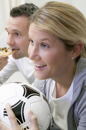 25 to 30 year olds: Young couple watching TV with football and pizza