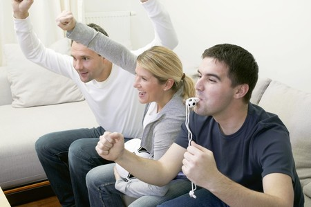 25 to 30 year olds: Friends with whistle & football cheering in front of TV LANG_EVOIMAGES