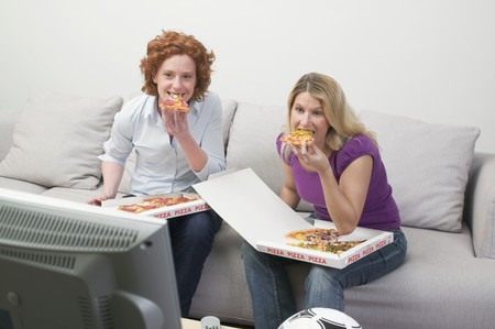 25 to 30 year olds: Two friends eating pizza while watching TV
