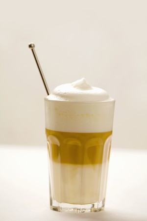 hot coffees: A glass of latte macchiato with coffee spoon LANG_EVOIMAGES
