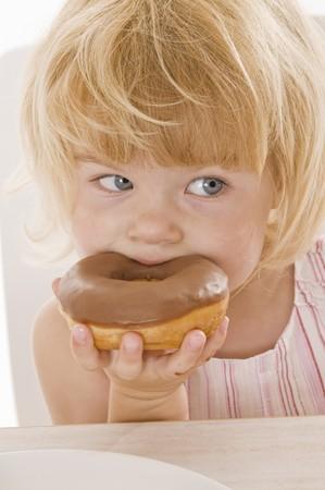 poco: Niña que come un donut con glaseado de chocolate