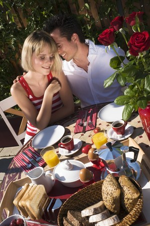25 to 30 year olds: Couple sitting at breakfast table out of doors LANG_EVOIMAGES