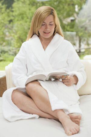 1 person: Woman in white bathrobe reading a book in the garden