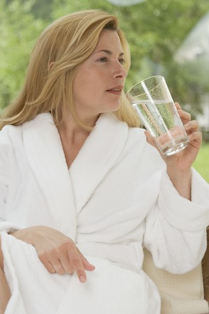 35 to 40 year olds: Woman in white bathrobe drinking glass of water in garden