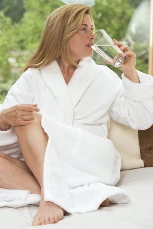 settle back: Woman in white bathrobe drinking glass of water in garden