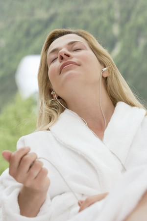 well beings: Woman in white bathrobe listening to music in garden LANG_EVOIMAGES