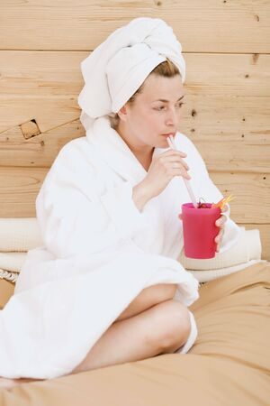 35 to 40 year olds: Woman in bathrobe drinking fruit cocktail