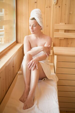 30 to 35 year olds: Woman sitting in a sauna LANG_EVOIMAGES