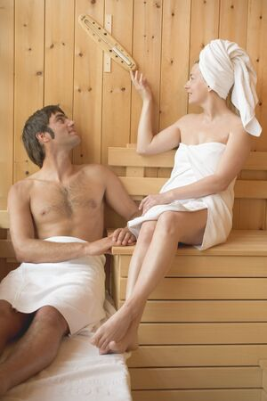 25 to 30 year olds: Man & woman sitting in sauna, woman turning hourglass over LANG_EVOIMAGES