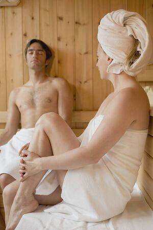 35 to 40 year olds: Man and woman sitting in a sauna LANG_EVOIMAGES
