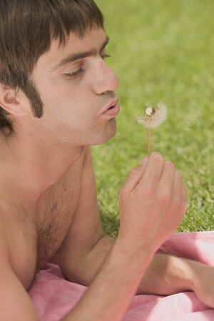 25 to 30 year olds: Man blowing a dandelion clock