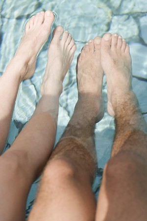 footcare: Man and woman dangling their feet in water