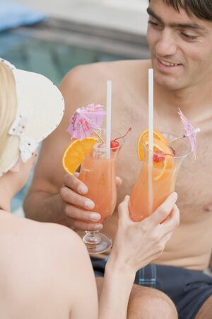 25 to 30 year olds: Man and woman with Planters Punch by pool