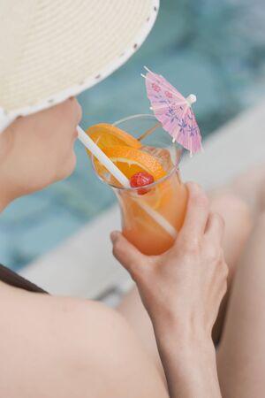 jardineras: Mujer bebiendo ponche de Planter en la piscina LANG_EVOIMAGES