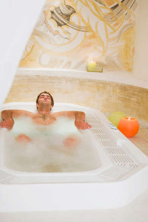 well beings: Young man lying in jacuzzi