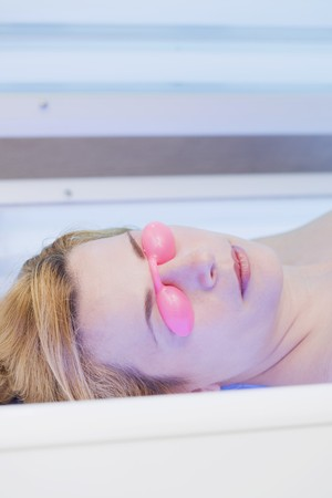 35 to 40 year olds: Blond woman in tanning goggles lying on tanning bed