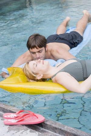 35 to 40 year olds: Man and woman on air beds in water LANG_EVOIMAGES
