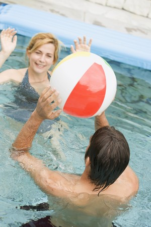 well beings: Man and woman playing with beach ball in swimming pool