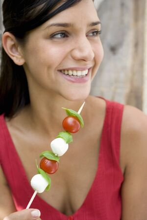 18 25 year old: Young woman with tomato and mozzarella skewer LANG_EVOIMAGES