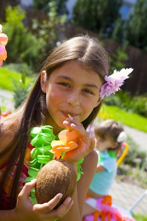 10 to 12 year olds: Girl drinking coconut milk out of coconut at childrens party LANG_EVOIMAGES