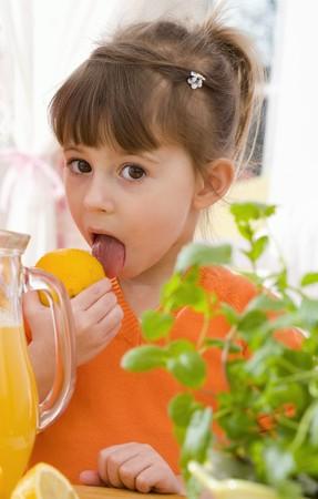 5 10 year old girl: Girl licking a lemon beside jug of lemonade