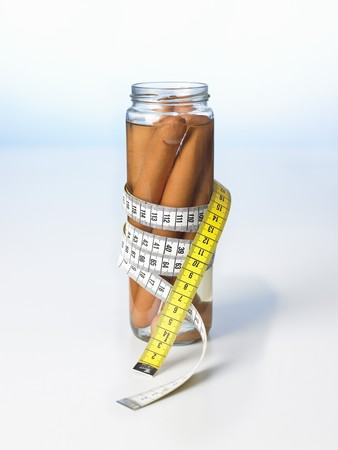 scalded sausage: Frankfurters in a jar with a tape measure wrapped around it