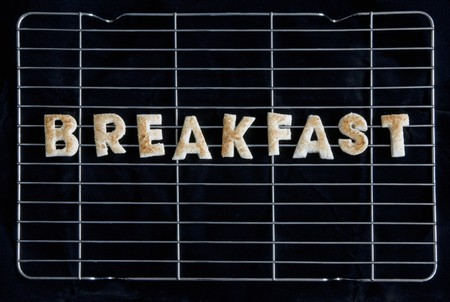 several breads: Toast letters spelling the word BREAKFAST on a rack
