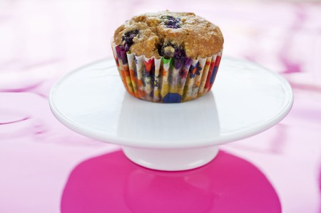 blueberry muffin: Blueberry Muffin with Colorful Wrapper on Pedestal Dish