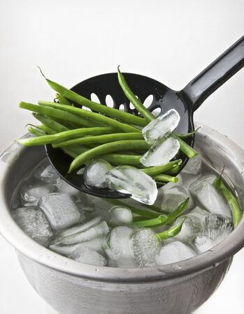 Quenched beans being removed from a bowl of iced water