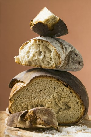 several breads: Rustic bread, two loaves with pieces cut off in a pile LANG_EVOIMAGES