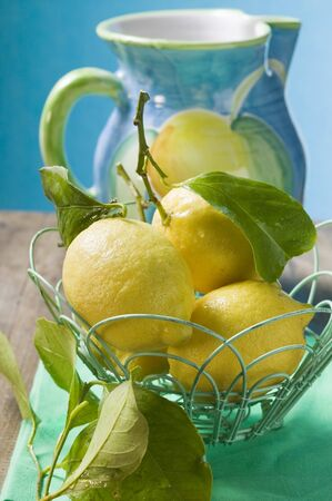 limon: Fresh lemons with leaves in wire basket LANG_EVOIMAGES